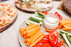 Pepino fresco, cenoura, paprika doce vermelha cortada nas listras em uma placa de corte de madeira verde-oliva Foto de Stock Royalty Free