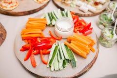 Pepino fresco, cenoura, paprika doce vermelha cortada nas listras em uma placa de corte de madeira verde-oliva Imagens de Stock Royalty Free