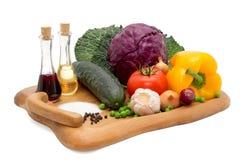 Pepino, pimienta, cebolla, ajo, hojas de la col, tomate y col roja en una meseta con aceite, vinagre, pimienta y sal Imagenes de archivo