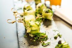 Pepino, queso feta y aceitunas negras Rolls en la bandeja de la comida de la pizarra fotografía de archivo