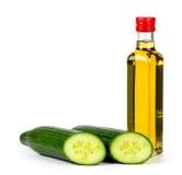 Pepino y aceite de oliva en un fondo blanco foto de archivo