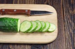 Pepino y cuchillo frescos cortados Foto de archivo