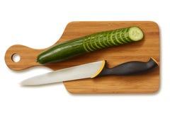 Pepino y cuchillo rebanados en la tarjeta de corte. Foto de archivo libre de regalías