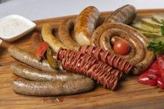 Pepinos conservados en vinagre, salchichas hervidas, queso con los tomates fritos, perejil y cereza en restaurante foto de archivo