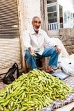 Pepinos de la venta del hombre en mercado Fotografía de archivo libre de regalías