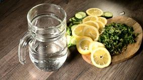 Pepinos del limón y hojas de menta cortados en una tabla de cortar de madera al lado de una garrafa de cristal con agua chispeant metrajes
