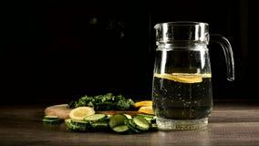 Pepinos del limón y hojas de menta cortados en una tabla de cortar de madera al lado de una garrafa de cristal con agua chispeant almacen de metraje de vídeo