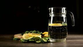 Pepinos del limón y hojas de menta cortados en una tabla de cortar de madera al lado de una garrafa de cristal con agua chispeant almacen de video