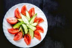 Pepinos e tomates e vegetais cortados em uma placa Fotos de Stock