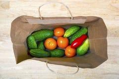Pepinos e tomates frescos em um pacote de papel Foto de Stock