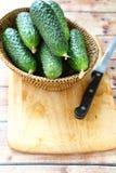 Pepinos em uma cesta na placa de corte Foto de Stock