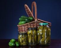Pepinos enlatados em um frasco e pepinos frescos em uma cesta fotos de stock royalty free