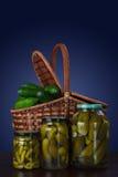 Pepinos enlatados em uns frascos e uma cesta de pepinos frescos Fotos de Stock