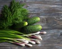 Pepinos frescos, cebolas verdes e aneto para a salada em uma superfície de madeira Imagens de Stock