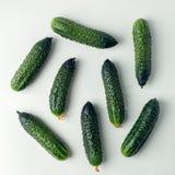 Pepinos frescos en el fondo ligero, comida orgánica de la nutrición, fondo mínimo sano del vegano fotografía de archivo libre de regalías