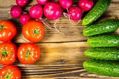 Pepinos, rábanos y tomates frescos en la tabla de madera Fotografía de archivo