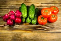 Pepinos, rabanetes e tomates frescos na tabela de madeira Fotografia de Stock Royalty Free