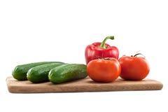 Pepinos, tomates y pimientas en tarjeta de madera Imágenes de archivo libres de regalías