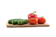 Pepinos, tomates y pimientas en tarjeta de madera Fotos de archivo libres de regalías