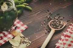 Pepinos verdes, pimenta, folha de louro na tabela de madeira Foto de Stock Royalty Free