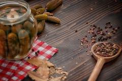 Pepinos verdes, pimienta, hoja de laurel en la tabla de madera Fotografía de archivo
