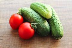 Pepinos y tomates en un fondo de madera, verduras foto de archivo libre de regalías