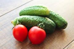 Pepinos y tomates en un fondo de madera, verduras fotografía de archivo libre de regalías