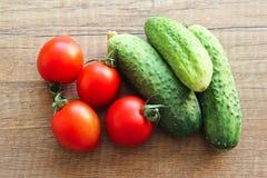 Pepinos y tomates en un fondo de madera, verduras imagenes de archivo