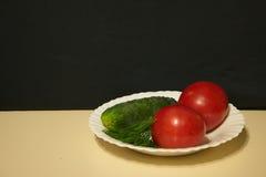 Pepinos y tomates en una placa foto de archivo