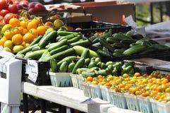 Pepinos y tomates para la venta en el mercado de un granjero Imagen de archivo libre de regalías
