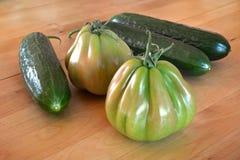 Pepinos y tomates verdes en un phfoto de madera del primer de la tabla fotos de archivo