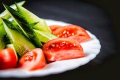 Pepinos y tomates y verduras cortados en una placa Fotos de archivo
