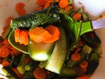 Pepinos y zanahorias en una cuchara Ensalada Fotografía de archivo