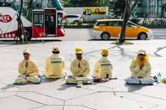 Pepita de la gente de Falun Dafa que se sienta en la calzada y la práctica para la mejora del uno mismo en Taipei, Taiwán fotografía de archivo