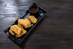 Pepita di pollo in piatto nero fotografie stock