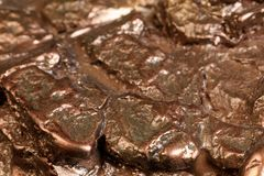 Pepita en bronce Un pequeño terrón del bronce en formas abstractas, modo foto de archivo