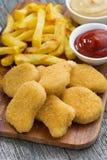 Pepitas de galinha com batatas fritas e molhos diferentes Foto de Stock