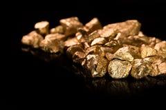 Pepitas de oro en fondo negro. imágenes de archivo libres de regalías