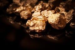 Pepitas de oro en fondo negro. imagenes de archivo