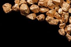 Pepitas de oro en fondo negro. imagen de archivo libre de regalías
