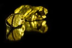 Pepitas de oro en fondo negro con la reflexión Imagen de archivo libre de regalías