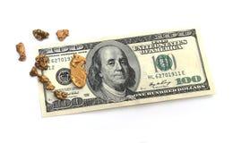 Pepitas de oro y cuenta de dólar hudred Imágenes de archivo libres de regalías
