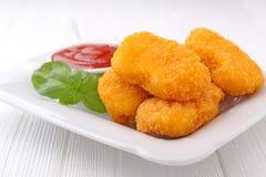 Pepitas de pollo con la salsa de tomate adornada con albahaca Imagen de archivo