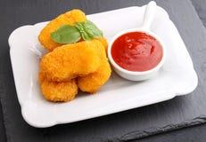 Pepitas de pollo con la salsa de tomate adornada con albahaca Imagen de archivo libre de regalías