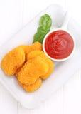 Pepitas de pollo con la salsa de tomate adornada con albahaca Foto de archivo