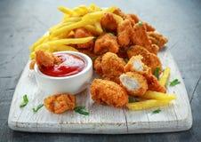 Pepitas de pollo curruscantes fritas con las patatas fritas y la salsa de tomate en el tablero blanco Imagen de archivo libre de regalías