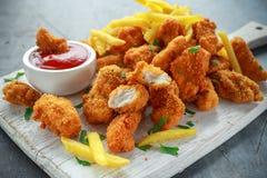 Pepitas de pollo curruscantes fritas con las patatas fritas y la salsa de tomate en el tablero blanco foto de archivo libre de regalías