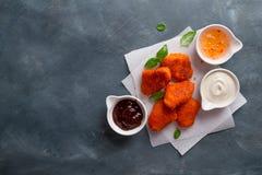 Pepitas de pollo curruscantes fritas con las salsas fotos de archivo