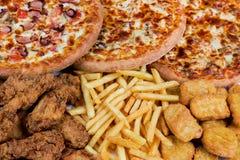 Pepitas de pollo de la comida rápida, piernas, pizzas y potatos de la fritada Imagenes de archivo