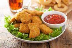 Pepitas de pollo de los alimentos de preparación rápida con la salsa de tomate, patatas fritas, cola Foto de archivo libre de regalías